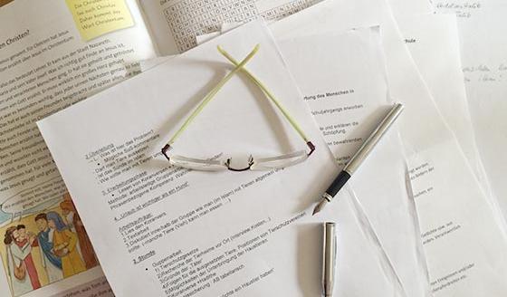 Füllhalter und Brille auf Papieren zum Thema Religionsunterricht